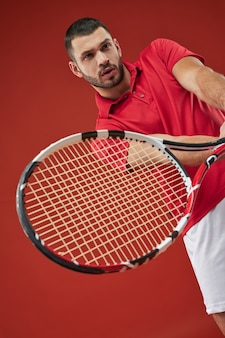 Close up portrait of bearded caucasian muscular male tennis player in red shirt training in sport club