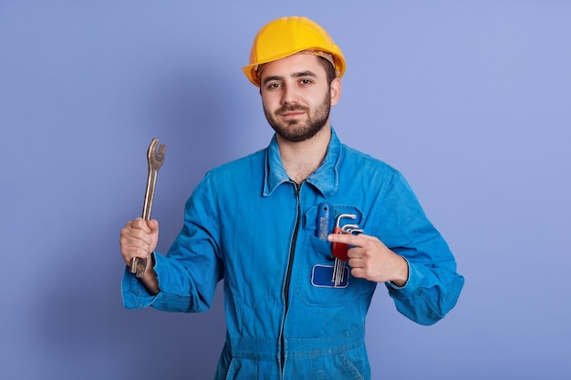 Close up portrait of bearded engineer with wrenches looking at camera and pointing at his tool with index finger, repairman posing against blue, mechanic dresses uniform and yellow hard hat.
