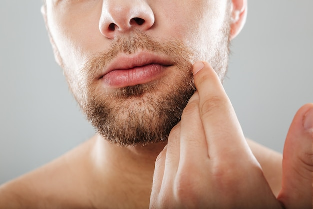 Close up portrait of bearded half men's face with hand