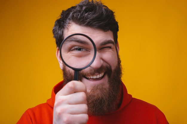 Close up portrait of a bearded man looking through a magnifying glass on yellow space.