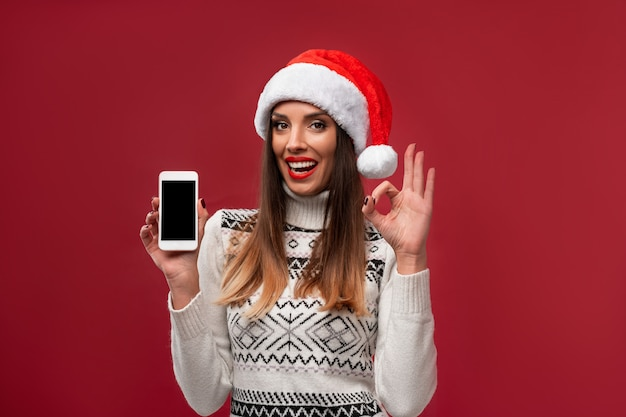 Close up portrait beautifiul caucasian woman in red santa hat on red  wall. christmas new year  concept. cute woman teeth smiling positive emotions with free copy space