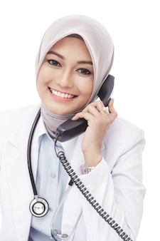 Close up portrait of beautiful asian female doctor talking on the phone