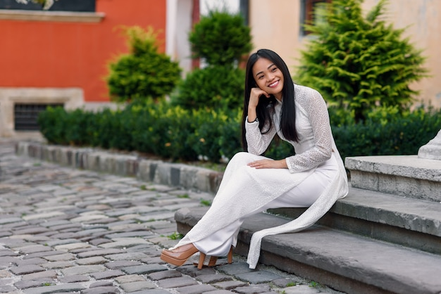 Close up portrait of beautiful asian woman dressed in ao dai white dress sitting on the stairs in courtyard.