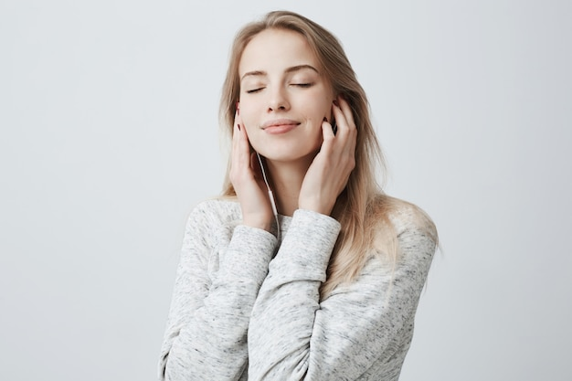 Close-up portrait of beautiful attractive european young woman in gray loose sweater, relaxing with closed eyes, listening to her favourite songs via white earphones, using music app.