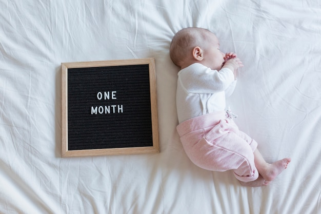 Close up portrait of a beautiful baby on white background at home. letter board vintage with one month message