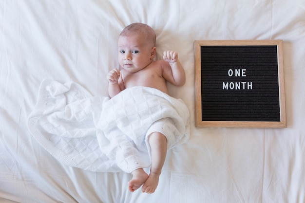Close up portrait of a beautiful baby on white background at home with a vintage letter board with message: one month