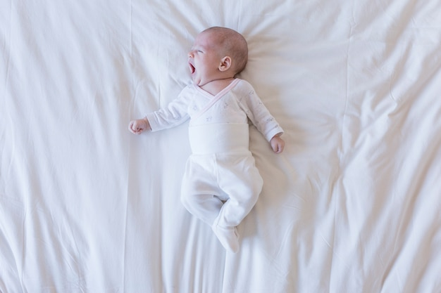 Close up portrait of a beautiful baby yawning on white background at home