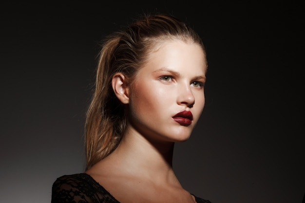 Close up portrait of a beautiful blonde girl with hair gathered in a ponytail, on dark background.