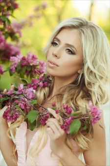 Close-up portrait of a beautiful blonde woman in a pink floral summer garden.