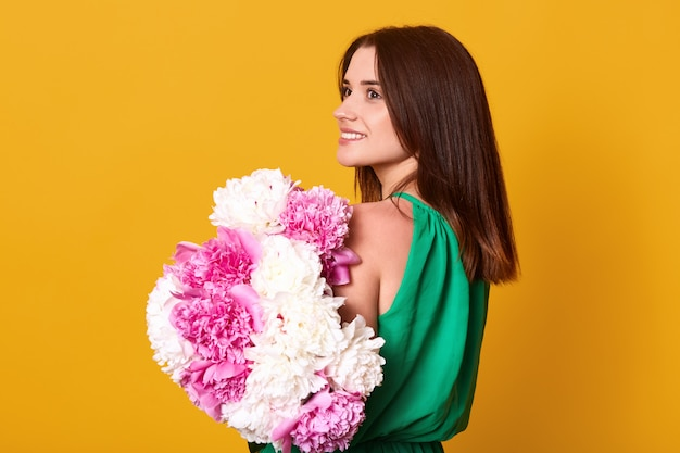 Close up portrait of beautiful brunette girl holds big bouquet with white and rose peonies.