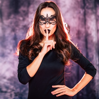 Close up portrait of a beautiful brunette woman in witch costume posing during a halloween party
