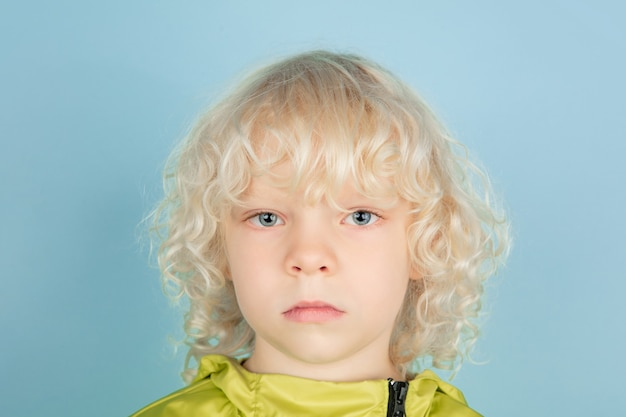 Close up portrait of beautiful caucasian little boy isolated on blue studio wall