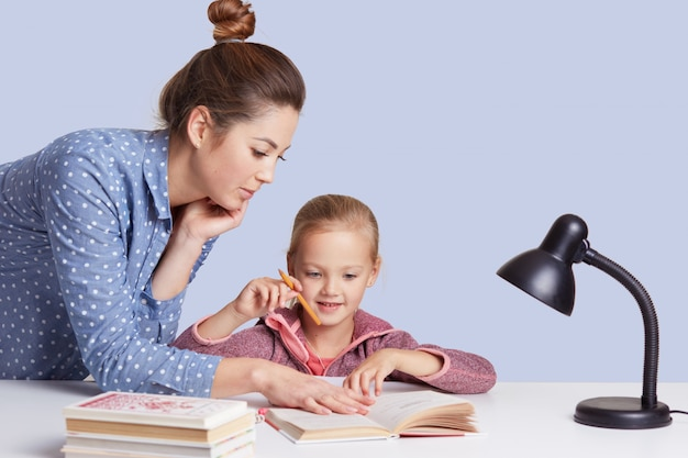 Close up portrait of beautiful caucasian woman helping her doughter to do school homework, female with bunch on head, wearing casual outfit, little cute girl sitting at table surrounded by books.