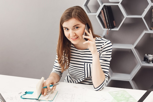 Close up portrait of beautiful cheerful young female freelance architect sitting at table in office, talking on phone with person from team, writing down work mistakes in notebook