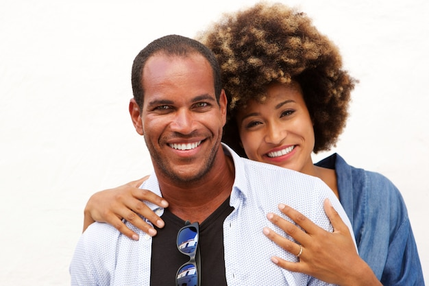 Close up portrait of beautiful couple smiling in embrace by white wall