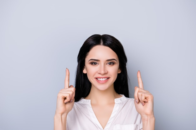 Close up portrait of beautiful cute smiling young  woman in formalwear with black hair pointing up at copy space above her head