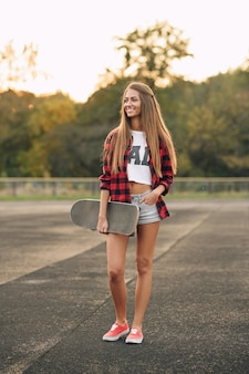 Close up portrait of a beautiful cute teen woman with a perfect body in red shirt, white t-shirt, shorts and red sneakers