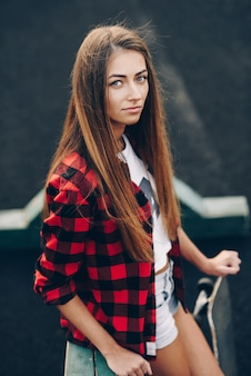Close up portrait of a beautiful cute young woman in red shirt, white t-shirt and short shorts