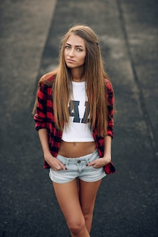 Close up portrait of a beautiful cute young woman with a perfect body in red shirt, white t-shirt and short shorts