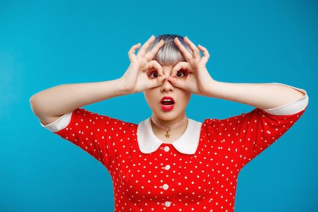 Chiuda sulla bella ragazza da bambola del ritratto con i capelli corti viola chiaro che portano il vestito rosso sopra la parete blu