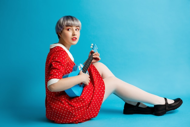Close up portrait of beautiful dollish girl with short light violet hair wearing red dress holding ukulele over blue wall