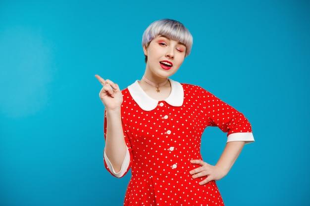 青い壁に赤いドレスを着て短いライトバイオレット髪の美しい人形のような女の子の肖像画を閉じる