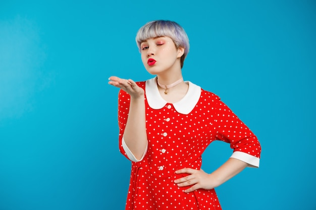 Close up portrait beautiful dollish girl with short light violet hair wearing red dress sending kiss over blue wall