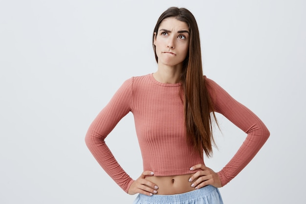 Close up portrait of beautiful funny young caucasian student girl with dark long hair in trendy clothes looking aside with thoughtful and confused expression, holding hands on waist