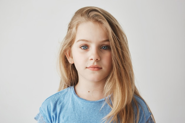 Close up portrait of beautiful little girl with light long hair and big blue eyes  with relaxed expression.