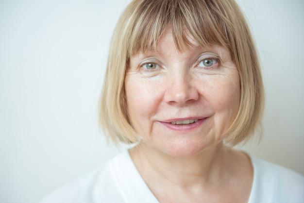 白い背景の肖像画の美しい年上の女性を閉じます。高齢者の日。高齢者の世話