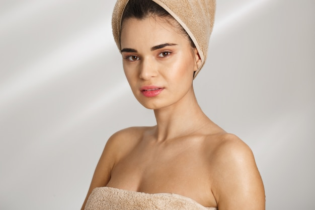 Close-up portrait of a beautiful posh young woman after bath standing covered in towel.