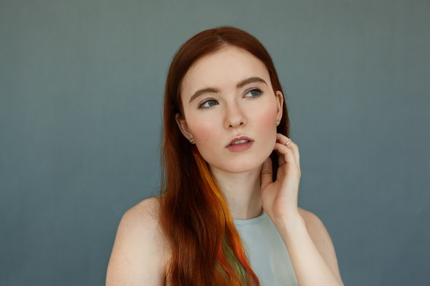 Close up portrait of a beautiful redhead female model with colored strands in hair and green eyes having thoughtful serious look, and mouth wide open. pretty ginger girl posing on blue wall