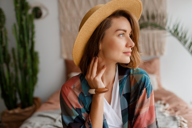Close up portrait of beautiful romantic woman in straw hat chilling over bohemian interior