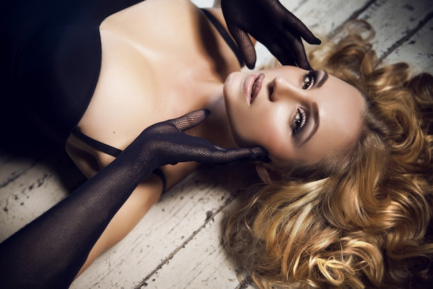 Close up portrait of beautiful sensual gorgeous young blonde lady with fashion make up and curly hairstyle in black bodysuit and netting gloves posing on a white wooden floor