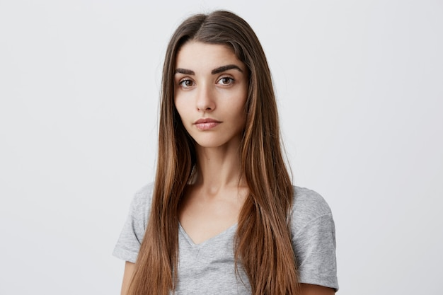 Close up portrait of beautiful serious dark-haired caucasian woman with long hairstyle in casual gray shirt  with relaxed and calm face expression. health and beauty.