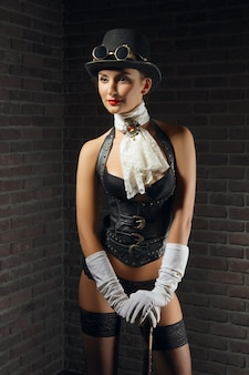 Close-up portrait of a beautiful steampunk girl in lingerie and stockings, hat and goggles.