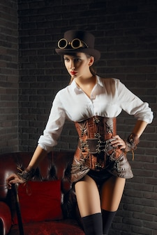 Close-up portrait of a beautiful steampunk girl in lingerie and stockings standing near old armchair.