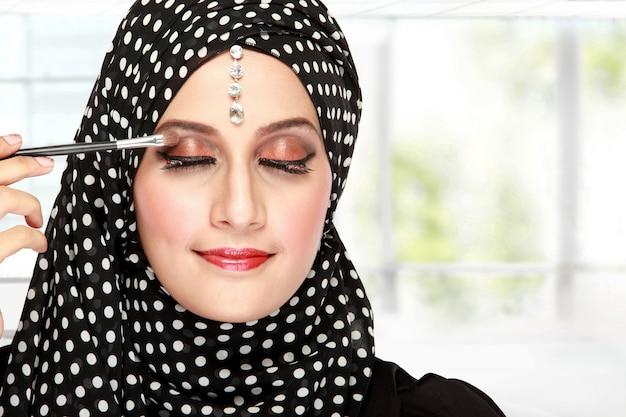 Close up portrait of beautiful woman applying mascara on her eyelashes