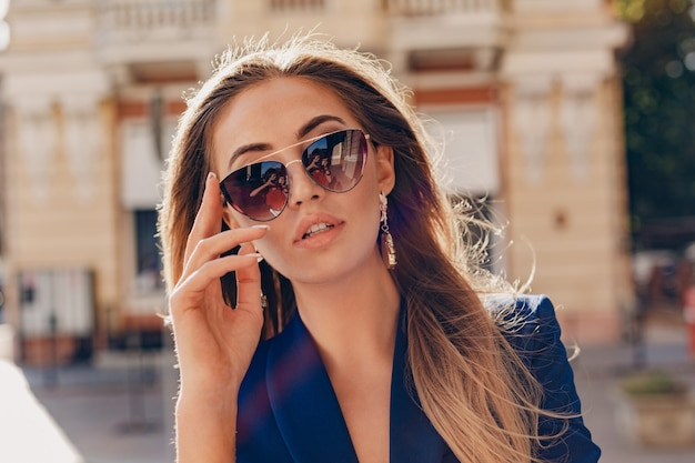 Close-up portrait of beautiful woman dressed in stylish blue jacket walking in autumn sunny street wearing elegant sunglasses and earrings