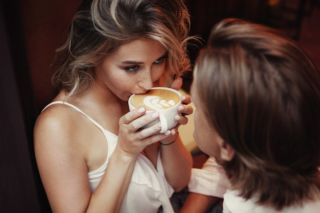 Close up portrait of beautiful woman drinking cup of coffee and gently looking at man. happy love couple having romantic dinner in cafe. toned warm.