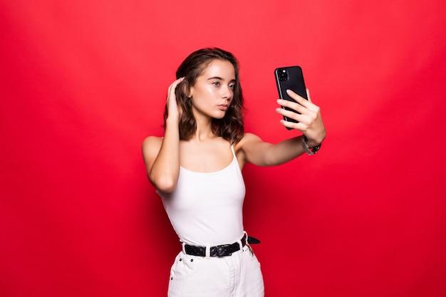 Chiuda sul ritratto che la bella donna prende selfie sulla parte anteriore dello smartphone moderno isolato sulla parete rossa di lustro