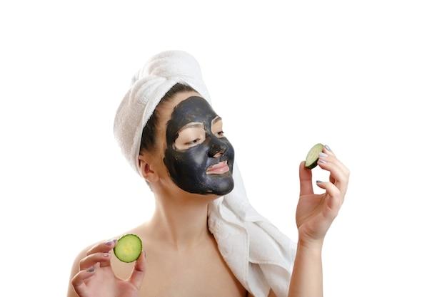 Крупным планом портрет красивой женщины с лицевой черной маской и ломтиками огурца в руках на белом фоне, девушка с белым полотенцем на голове
