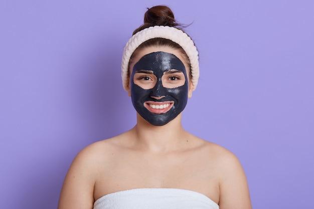 Chiuda sul ritratto di bella donna con maschera nera facciale isolata sopra il muro lilla, ragazza con un asciugamano bianco sul suo corpo e spalle nude, sorriso soddisfatto e felice, facendo la procedura di pulizia.