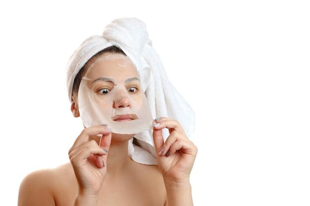 Крупным планом портрет красивой женщины с лицевой маской на белом фоне, снимает маску, девушка с белым полотенцем на голове