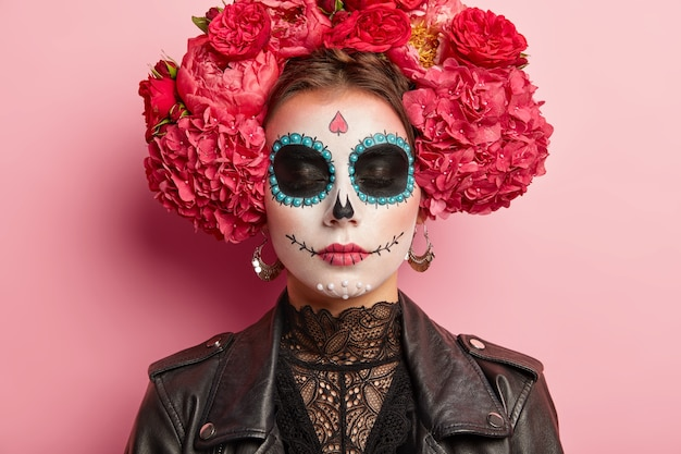 Close up portrait of beautiful woman with traditional mexican face painting, has eyes shut, wears wreath made of aromatic flowers, black attire, poses over pink wall