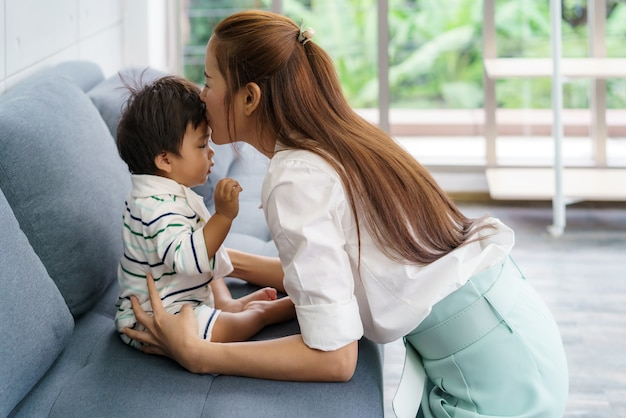 Close up portrait of beautiful young asian mother kissing her newborn baby to love asia woman lifestyle mother's day concept with copy space.
