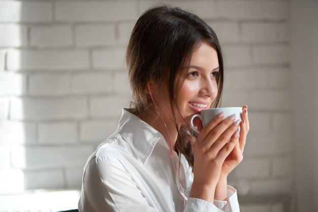 Close up portrait of a beautiful young dark haired woman smiling happily enjoying her morning cup of coffee looking away positivity beauty lifestyle relax leisure urban living youth recreation.