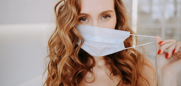 Close up portrait of beautiful young european woman wearing protective mask for corona virus prevention, hygiene to stop spreading coronavirus. avoid contaminating corona virus covid-19 concept