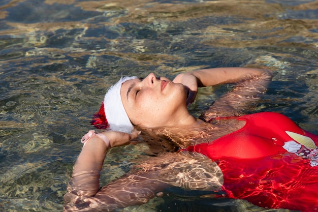 Close-up portrait of a beautiful young girl with freckles, in a red swimsuit and santa claus hat, lying in the sea water of the red sea.