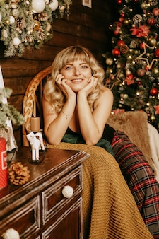 Close up portrait of beautiful young girl with long curly hair on a christmas background with lights magic warm new year photo cozy interior